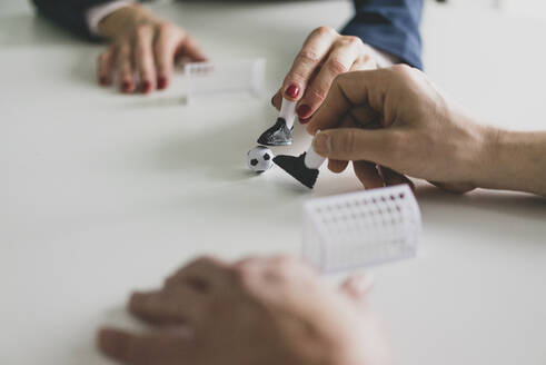 Close-up of businesswoman and businessman playing table football in office - MOEF02551