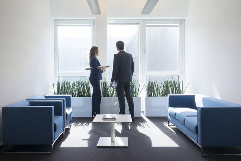 Businesswoman and businessman looking out of window in office lounge - MOEF02569
