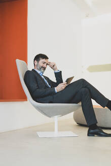 Mature businessman sitting in chair using tablet - MOEF02584