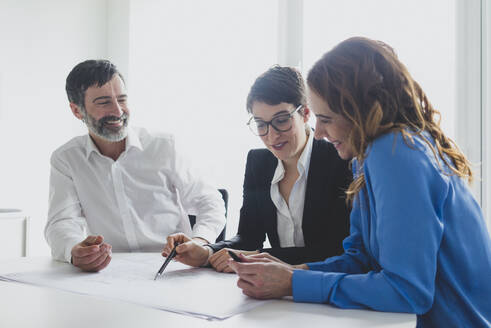 Businessman and two businesswomen working on plan on desk in office - MOEF02599