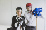 Portrait of businesswoman and businessman wearing ice hockey equipment in office - MOEF02635