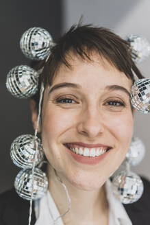 Portait of happy young businesswoman  wearing mirror balls - MOEF02641