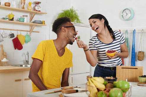 Multiethnic couple breakfasting together in the kitchen - IGGF01398