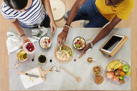Multiethnic couple breakfasting together in the kitchen, from above - IGGF01404