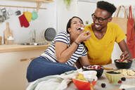 Multiethnic couple breakfasting together in the kitchen - IGGF01407