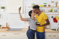 Multiethnic couple breakfasting together in the kitchen - IGGF01410