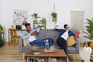 Multiethnic couple spending time together at living room, woman using tablet and man smartphone - IGGF01413