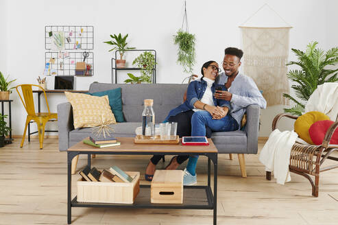 Multiethnic couple spending time together at living room and using smartphone - IGGF01416