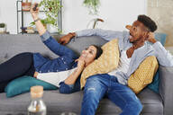 Multiethnic couple spending time together at living room and taking a selfie - IGGF01425