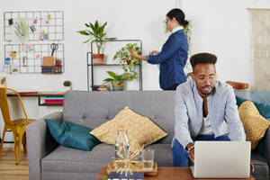 Multiethnic couple spending time together at living room, man using laptop - IGGF01428