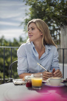 Portrait of woman, working at cafe table, outdoors - AJOF00040