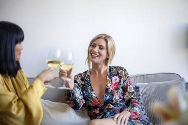 Two friends sittng on couch, drinking wine, smiling - AJOF00058