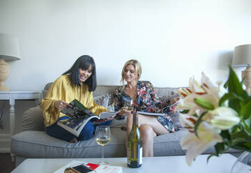 Friends sitting on couch, reading magazines, drinking wine - AJOF00064