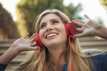 Portrait of smiling woman, listening to music on red headphones - AJOF00073