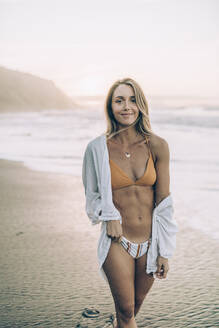 Young blond woman wearing bikini and white dress at the beach during sunrise - MTBF00110