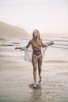 Young blond woman wearing bikini at the beach during sunrise - MTBF00113