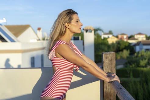 Portrait of woman standing on roof terrace looking at distance, Sevilla, Spain - ERRF02002