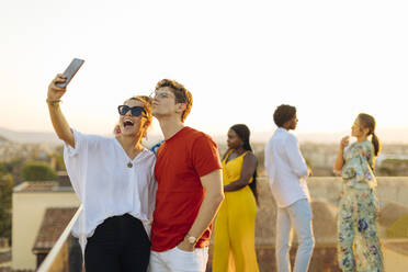 Young woman and man taking a selfie during a party in the evening - SODF00176