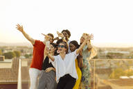 Group of happy multi-ethnic friends taking a selfie during a party in the evening - SODF00179