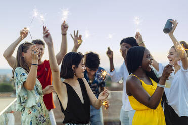 Group of happy multi-ethnic friends celebrating a party in the evening, holding sparklers - SODF00185