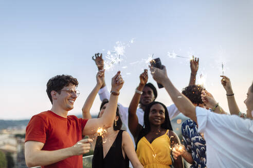 Group of happy multi-ethnic friends celebrating a party in the evening, holding sparklers - SODF00188