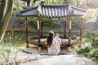 Mother and baby girl visiting pagoda in the Secret Garden, Changdeokgung, Seoul, South Korea - GEMF03264