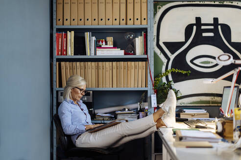 Mature woman working in architct's office, with feet up - SODF00212