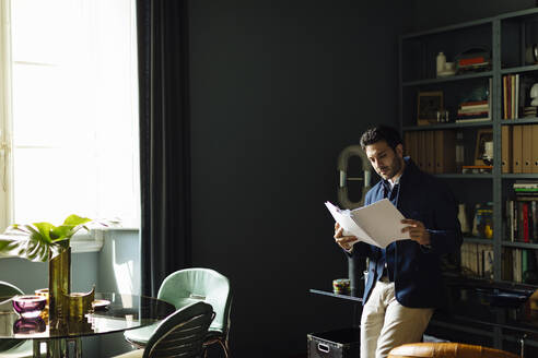 Creative professional stanong in his office, reading documents - SODF00233
