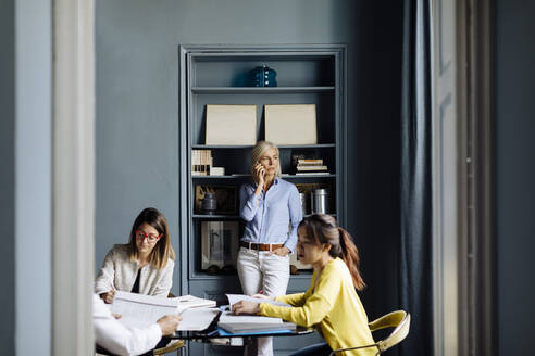 Woman talking on the phone, while colleagues having a project meeting - SODF00245