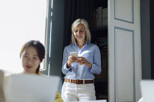 Mature woman using smartphone in background, while colleague is working at desk - SODF00251