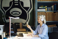 Mature woman talking on the phone with headphones, sitting in architect's office - SODF00269