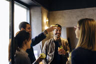 Colleagues celebrating after work in a bar - SODF00275