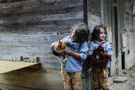 Two kids holding chickens on an organic farm - SODF00305