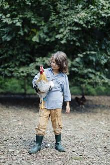 Boy holding chicken on an organic farm - SODF00311