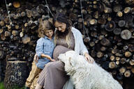 Pregnant mother with son and dog relaxing at stack of wood - SODF00314