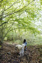 Rear view of child with dog in the forest - SODF00320