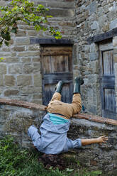 Playful boy doing a headstand at a rustic farmhouse - SODF00326