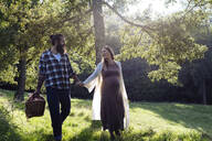 Happy man walking with pregnant wife in the countryside - SODF00329