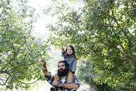 Father with kid on his shoulders in an orchard - SODF00332