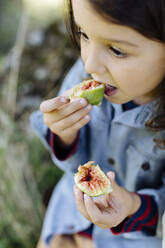 Child eating a fig outdoors - SODF00341