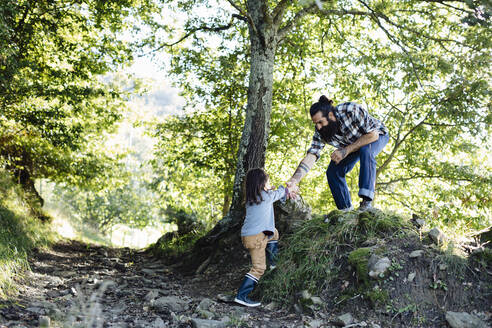 Boy reaching out for father's hand in the forest - SODF00344