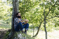 Man with beard sitting at tree trunk in the forest - SODF00347