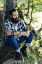 Man with beard sitting at tree trunk in the forest - SODF00350