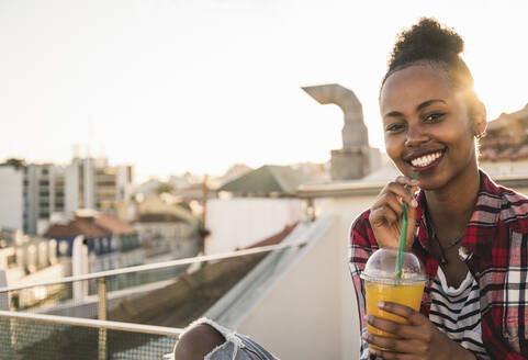 Portrait of happy young woman having a drink on rooftop at sunset - UUF19454