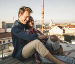 Relaxed affectionate young couple sitting on rooftop in the evening - UUF19478