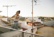 Happy young woman standing on rooftop at sunset listening to music with headphones - UUF19481