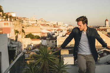 Young man standing on rooftop at sunset, Lisbon, Portugal - UUF19484