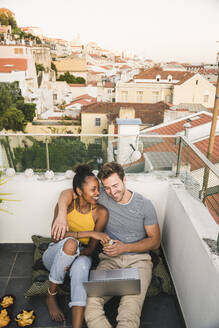 Happy young couple with laptop sitting on rooftop in the evening, Lisbon, Portugal - UUF19493