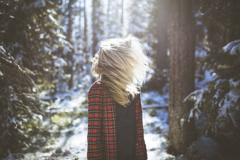 Woman shaking head while standing in forest during winter - CAVF68278