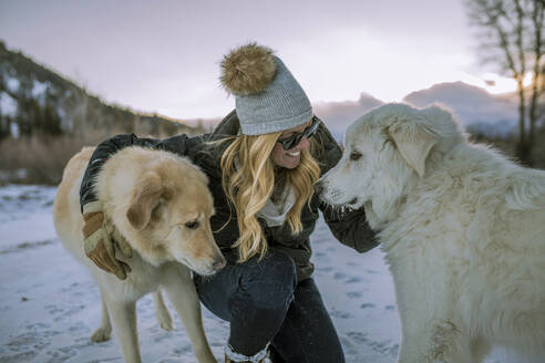 Happy woman stroking dogs while crouching on snowy field against sky during sunset - CAVF68281